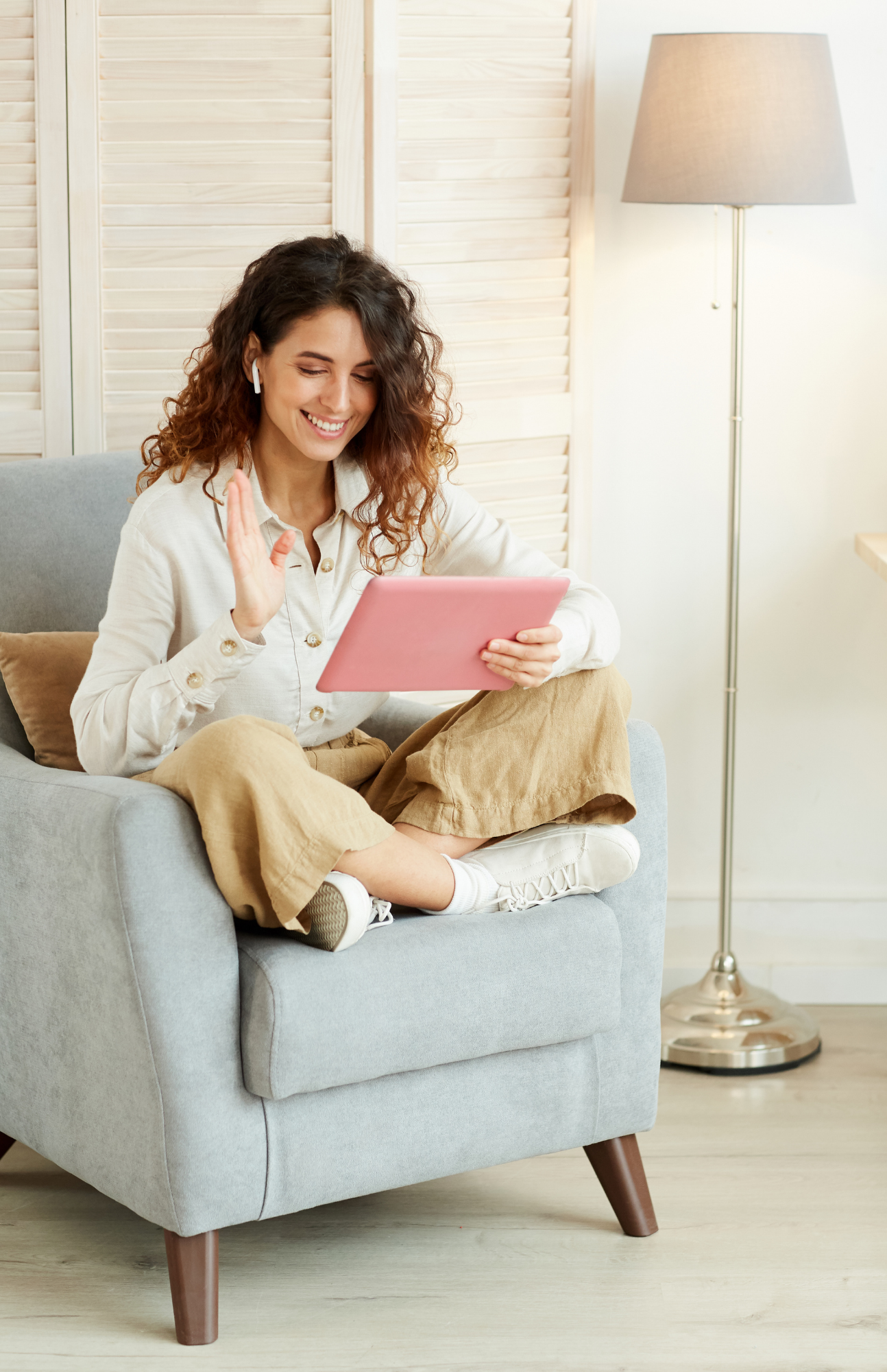 A woman sitting on a chair using virtual outplacement services on a tablet